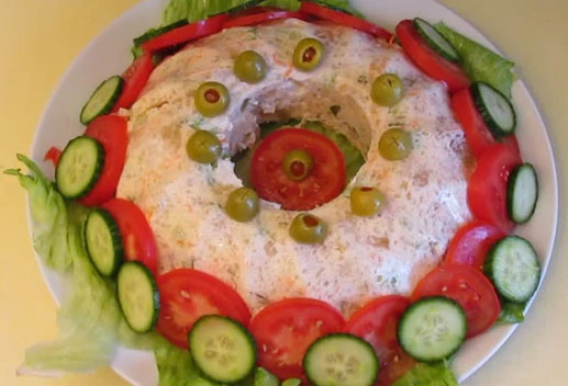 Jellied chicken salad garnished with tomato and cucumber
